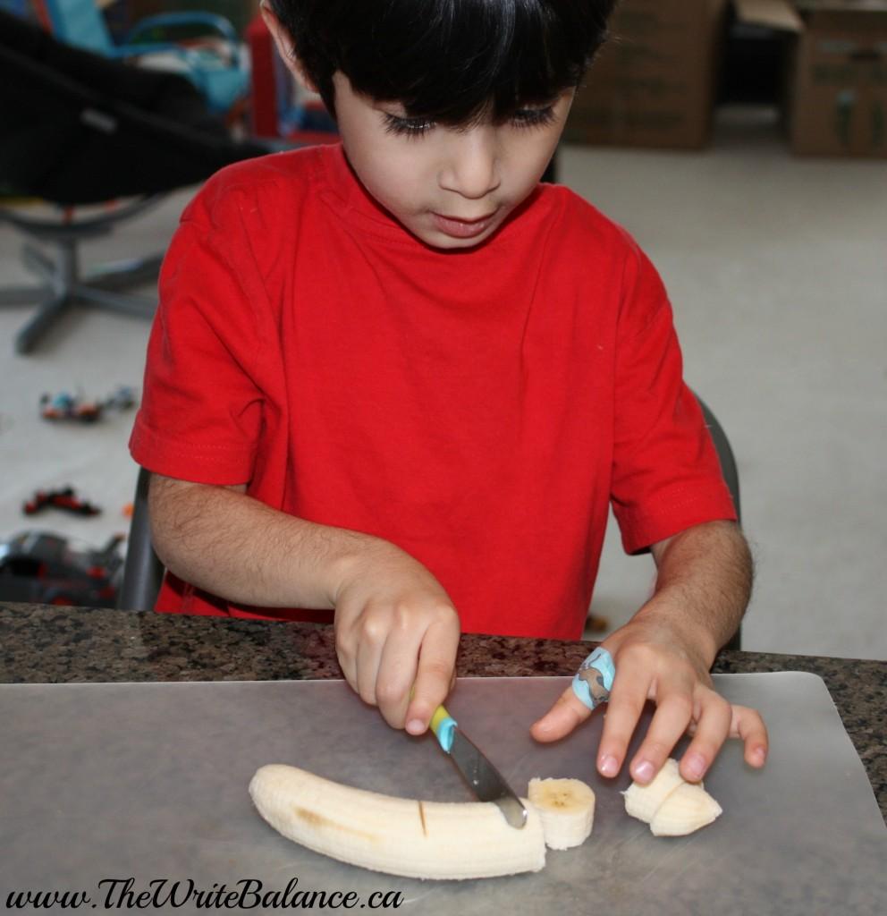 toddler cutting bananas